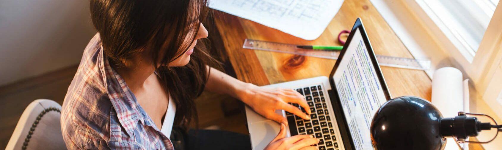 Suchmaschinenoptimierung Yoast mit Wordpress: Junge Frau checkt Google Suchergebnisse auf ihrem Laptop