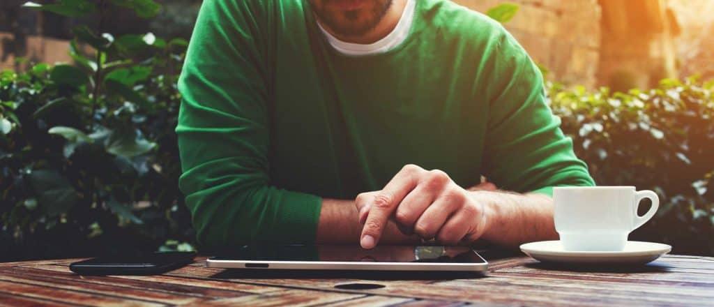 Mann in grünem Pulli analysiert am Tablet SEO Fehler