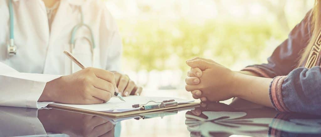 Marketing für Ärzte: Arzt macht Notizen bei Erstbesprechung mit neuem Patienten