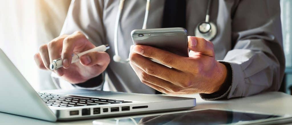 Klinikmarketing: Arzt prüft die Klinikinformationen im Internet mit Laptop und Handy