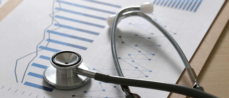 Praxismarketing für Ärzte: Stethoskop liegt auf Unterlagen mit Erfolgskennzahlen der Praxis