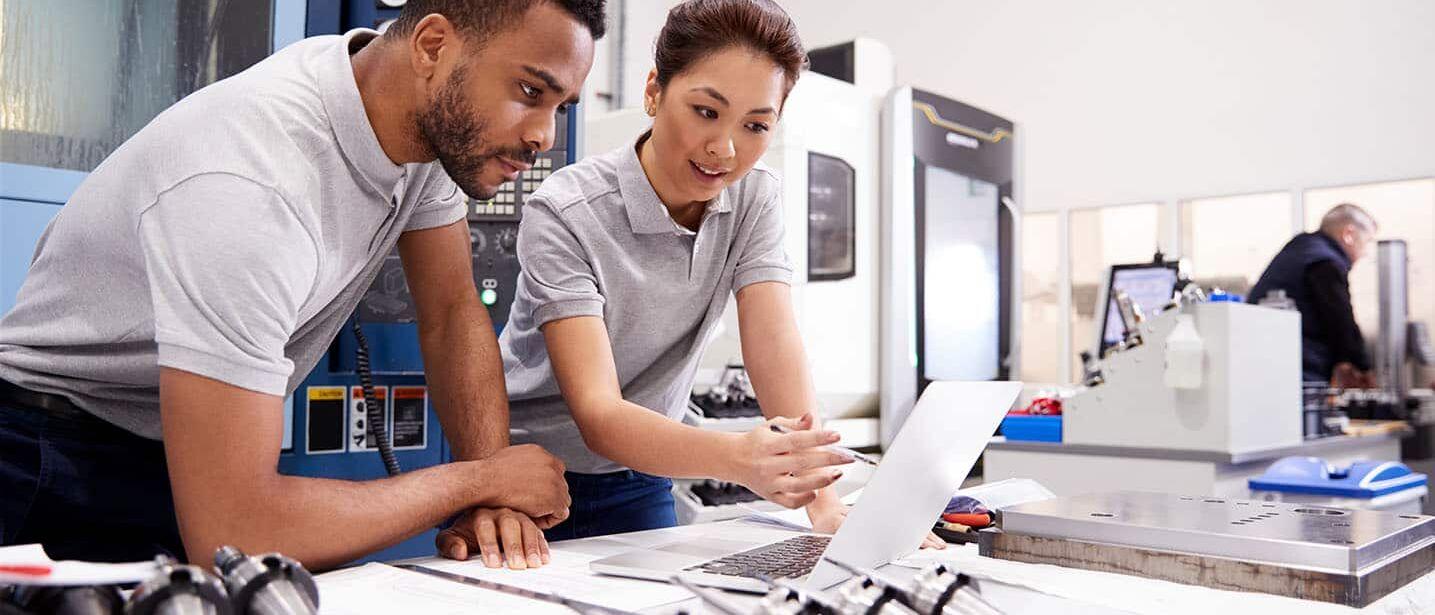 B2B Online Marketing im Maschinenbau: Zwei Maschinenbauer besprechen eine Marketingstrategie am Laptop
