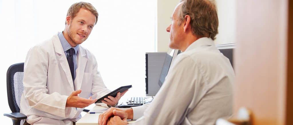 Online-Marketing für Ärzte zeigt Wirkung und ein Arzt begrüßt seinen neuen Patienten in seiner Praxis