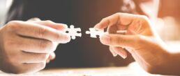 Hände halten zwei Puzzleteile aneinander
